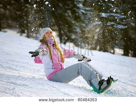 Happy smiling girl with lifted hands on snowboard about to slide downhill the mountain