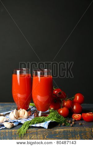 Glasses of tasty tomato juice and fresh tomatoes on table, on grey background