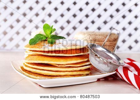 Stack of pancakes on plate with bank of jam on table and wooden lattice background