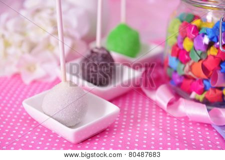Sweet cake pops on table on bright background