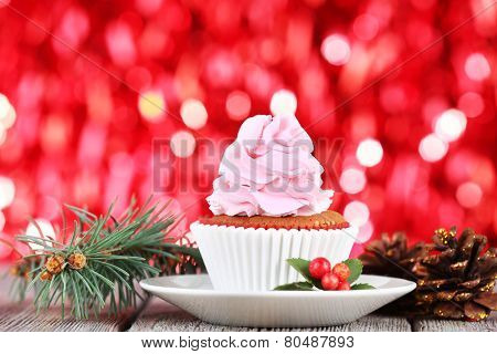 Cup-cake with cream on saucer and Christmas decoration on wooden table and shine brightly background