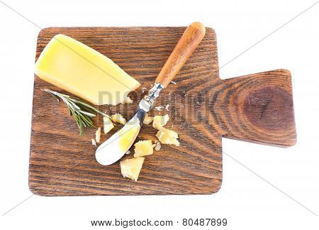 Crumbled Parmesan cheese with sprig of rosemary and knife on cutting board isolated on white