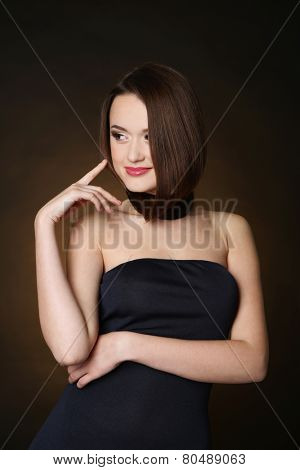 Beautiful young woman with long hair on dark brown background