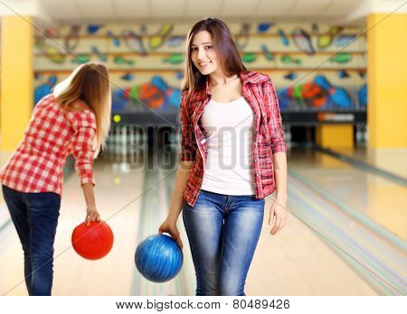 Young women holding bowling ball in club