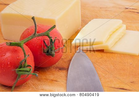 Piece Of Cheese And Slices Of Cheese With  Tomatoes On A Wodden Board