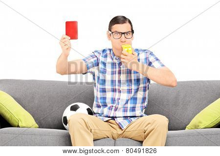 Angry man blowing a whistle and holding a red card isolated against white background