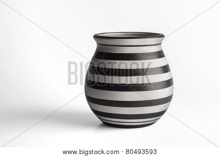 An earthen pot painted with black and white stripes.