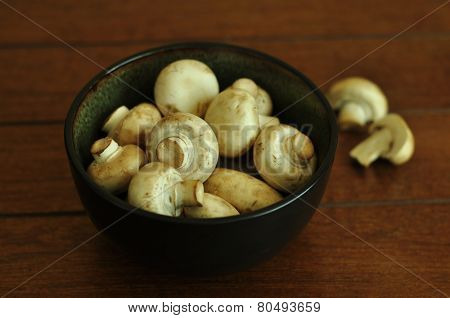 A bowl full of white button mushrooms on wooden background.