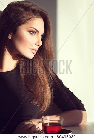 Beautiful Brunette Girl Drinking Tea or Coffee in Cafe. Beauty Model Woman with the Cup of Hot Beverage. Warm Colors Toned