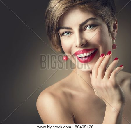 Portrait of young beauty woman with bob hairstyle and bare shoulders, isolated on dark background. Happy smiling lady with shot brown hair and bright make-up wearing  accessories.