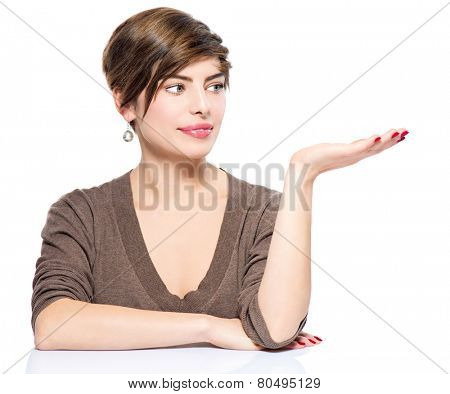 Young beauty woman with bob showing empty copy space on the open hand palm for text, white background. Happy girl presenting point watching on it. Proposing a product. Gestures for advertisement.