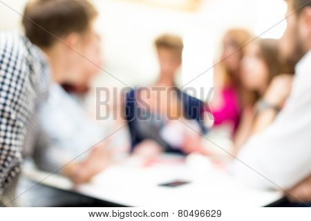 Image of business friends discussing brainstorming and ideas at meeting inside beautiful modern building place (Note: the image is out of focus, suitable as background)