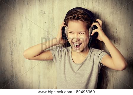 Cool teen girl enjoys the music in headphones. Studio shot.