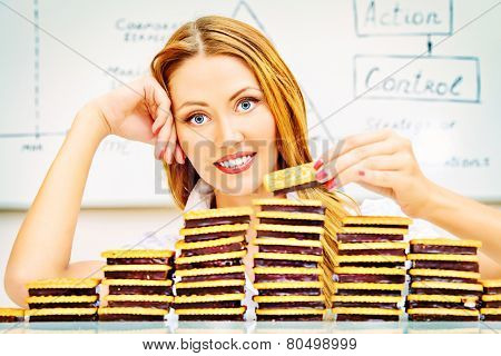 Beautiful businesswoman posing with cookies laid out in the form of diagrams. Business concept. Confectionary. Food industry.