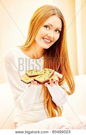 Happy slim girl with pleasure eats tasty cookies with chocolate. Healthy eating. Diet.