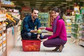foto of department store  - Beautiful Young Couple Shopping For Fruits And Vegetables In Produce Department Of A Grocery Store  - JPG