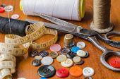 picture of sewing  - A collection of sewing tools and supplies in a sewing kit on woodem table - JPG