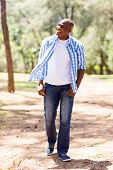stock photo of walking away  - casual young african american man walking in the park and looking away - JPG