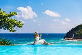 picture of infinity pool  - Beautiful young bride in a wedding dress sitting on the edge of the infinity - JPG