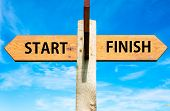 picture of start over  - Wooden signpost with two opposite arrows over clear blue sky Start versus Finish messages - JPG