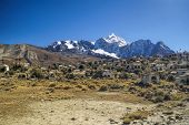 stock photo of graveyard  - Graveyard with Huayna Potosi mountain in the background peak in Bolivian Andes - JPG