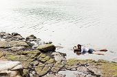 foto of accident victim  - View of a young woman washed up on rocks at the edge of a river possible boating accident victim - JPG