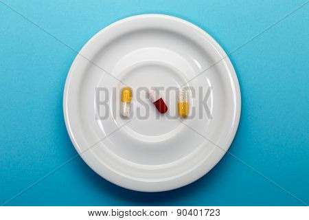 Three colorful capsules on a plate