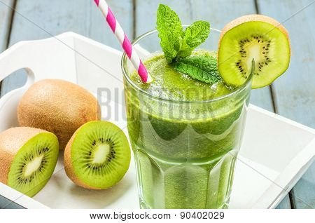 A Green Smoothie On A Tray With Kiwi