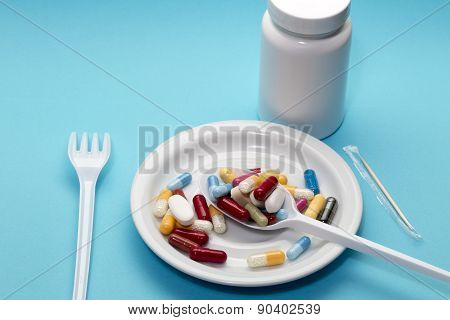 Different pills on a plate with bottle