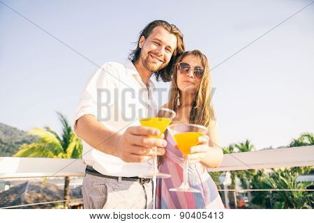 Couple Drinking Cocktails At Bar