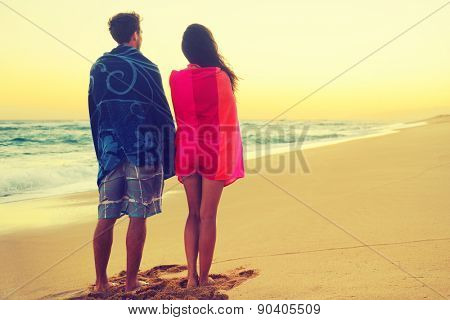 Romantic couple bathing with towels on beach sunset. Portrait of happy young couple looking at sunrise ocean sea view during holidays vacation travel. Asian woman, Caucasian man.