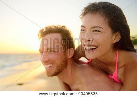 Beach couple laughing in love having fun romance on travel honeymoon vacation summer holidays. Young happy people, Asian woman and Caucasian man embracing outdoors on tropical beach in casual wear.