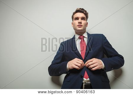 Young attractive business man closing his jacket while looking away from the camera.