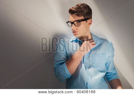 Handsome young casual man posing on grey studio background looking away from the camera.