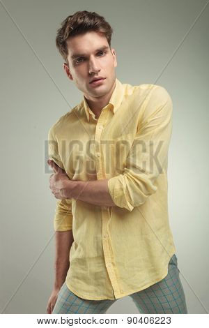 Young casual fashion man holding his right arm with his left hand.