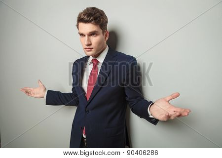 Handsome young business man standing with his arms open, looking away from the camera.