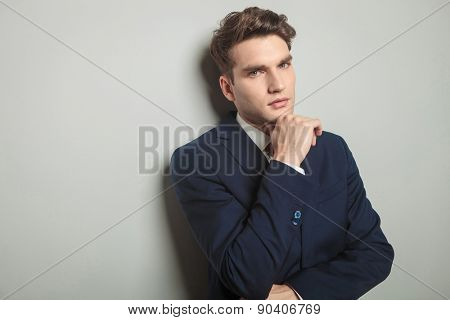Close up picture of a handsome young business man thinking while holding his hand to his chin.