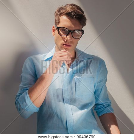 Portrait of a handsome casual man leaning on a wall while holding his hand to the chin.