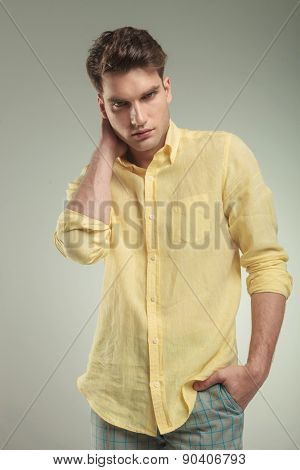 Serious young fashion man holding his right hand to his neck while the left one is in his pocket.