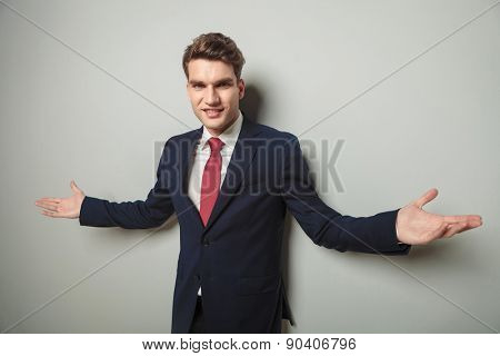 Happy young business man welcoming you with his arm open.
