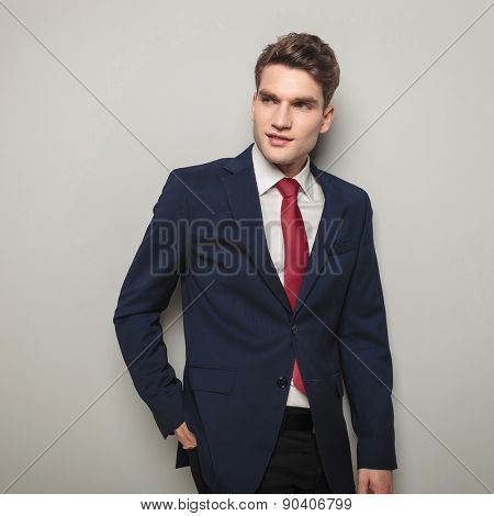 Attractive young business man smiling while holding his hand in the back pocket.