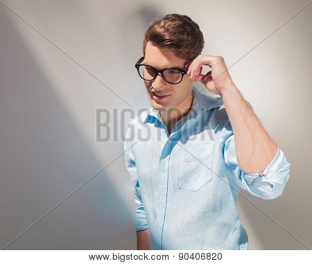 Smiling young casual man fixing his glasses while looking down.