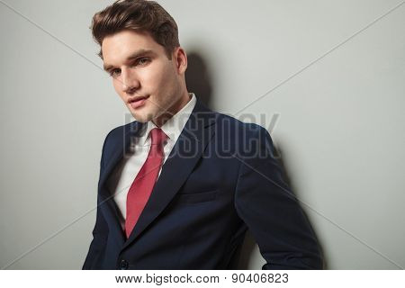 Close up picture of a handsome young business man leaning on a wall while looking at the camera.