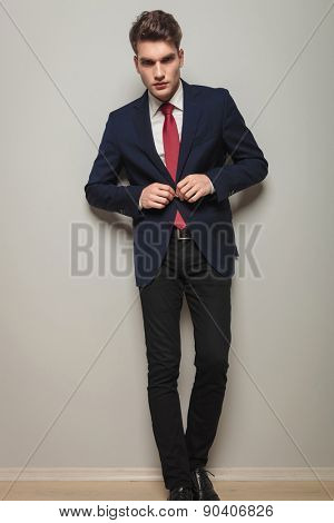 Full body picture of a young handsome business man opening his jacket.