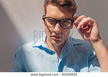 Close up picture of a handsome casual man taking off his glasses.