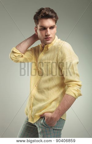 Side view of a young fashion man looking down while holding his hand in pocket.
