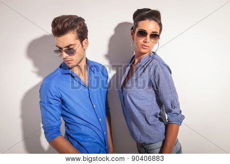 Man and woman posing against a grey wall both looking away from the camera.