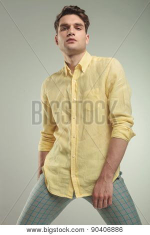 Arrogant young handsome man posing on grey studio background.