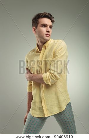 Side view picture of a young casual man holding his right arm with his left hand, looking away from the camera.