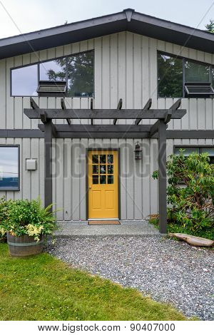 Entrance of a luxury mid-century modern cottage house with yellow door.